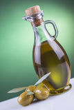 Botella y aceitunas del aceite de oliva en fondo verde Imagen de archivo libre de regalías