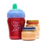 Botella y alimento para el bebé en un fondo blanco Imagen de archivo libre de regalías