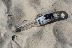 Botella y casquillo vacíos de Corona Extra en la playa fotografía de archivo libre de regalías