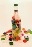 Botella y casquillos plásticos Imagen de archivo libre de regalías