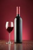 Botella y de cristal por completo del vino rojo sobre un contexto rojo Imágenes de archivo libres de regalías