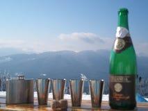 Botella y frasco con cuatro vidrios contra las montañas Fotografía de archivo libre de regalías