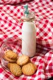 Botella y galletas de leche en un bol de vidrio Fotografía de archivo