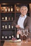 Botella y mirada de vino sonriente de la abertura del hombre mayor de la cámara, estante con el vino en el fondo Imágenes de archivo libres de regalías