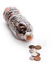 Botella y monedas plásticas Fotos de archivo libres de regalías