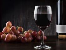 Botella y uvas de copa de vino en un fondo de madera Fotos de archivo