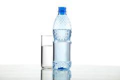 Botella y vidrio con agua en el fondo blanco Fotografía de archivo libre de regalías