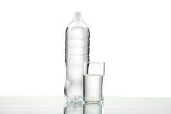 Botella y vidrio con agua en el fondo blanco Fotos de archivo libres de regalías