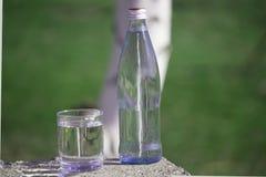 Botella y vidrio con el agua dulce en fondo de la hierba imagenes de archivo