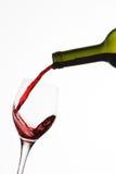 Botella y vidrio con el chapoteo del vino rojo Foto de archivo