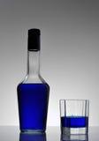 Botella y vidrio con el líquido azul Imagenes de archivo