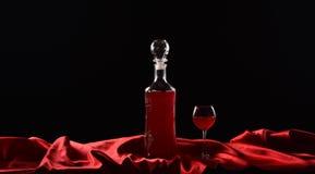 Botella y vidrio con el vino rojo en fondo negro con el paño rojo, tela de satén, seda Fotos de archivo libres de regalías