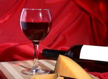Botella y vidrio con las uvas de vino rojo y los chees en la tabla de madera Fotografía de archivo
