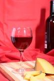 Botella y vidrio con las uvas de vino rojo y los chees en la tabla de madera Imagenes de archivo