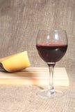 Botella y vidrio con las uvas de vino rojo y los chees en la tabla de madera Fotos de archivo libres de regalías
