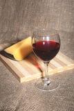 Botella y vidrio con las uvas de vino rojo y los chees en la tabla de madera Imagen de archivo libre de regalías