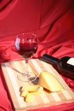 Botella y vidrio con las uvas de vino rojo y los chees en la tabla de madera Imágenes de archivo libres de regalías
