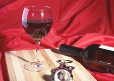 Botella y vidrio con las uvas de vino rojo y los chees en la tabla de madera Imagen de archivo