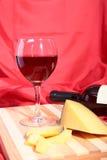Botella y vidrio con las uvas de vino rojo y los chees en la tabla de madera Foto de archivo libre de regalías