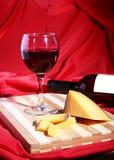 Botella y vidrio con las uvas de vino rojo y los chees en la tabla de madera Foto de archivo