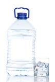 Botella y vidrio de agua mineral con las gotitas Imágenes de archivo libres de regalías