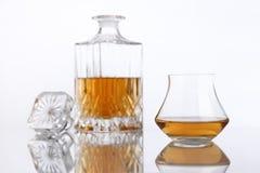 Botella y vidrio de brandy en una tabla blanca Fotografía de archivo