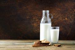 Botella y vidrio de la leche, pan del trigo integral en la tabla de madera, fondo oscuro Mañana soleada, espacio de la copia Foto de archivo