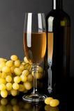 Botella y vidrio de vino blanco con las uvas Imagen de archivo