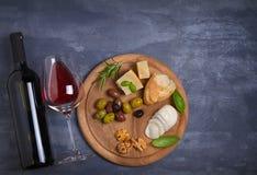 Botella y vidrio de vino con queso, las aceitunas, el pan, las nueces y el romero en fondo oscuro Concepto del vino y de la comid Imagen de archivo libre de regalías