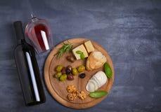 Botella y vidrio de vino con queso, las aceitunas, el pan, las nueces y el romero en fondo oscuro Concepto del vino y de la comid Foto de archivo libre de regalías