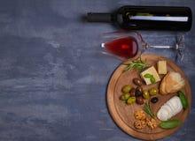 Botella y vidrio de vino con queso, las aceitunas, el pan, las nueces y el romero en fondo oscuro Concepto del vino y de la comid Fotografía de archivo libre de regalías