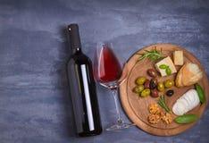 Botella y vidrio de vino con queso, las aceitunas, el pan, las nueces y el romero en fondo oscuro Concepto del vino y de la comid Fotografía de archivo