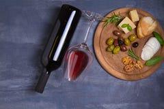 Botella y vidrio de vino con queso, las aceitunas, el pan, las nueces y el romero en fondo oscuro Concepto del vino y de la comid Imagenes de archivo