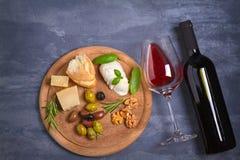 Botella y vidrio de vino con queso, las aceitunas, el pan, las nueces y el romero en fondo oscuro Concepto del vino y de la comid Fotos de archivo libres de regalías