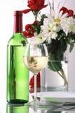 Botella y vidrio de vino en el fondo blanco Foto de archivo