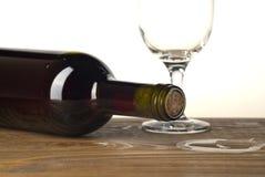 Botella y vidrio de vino en fondo de madera foto de archivo