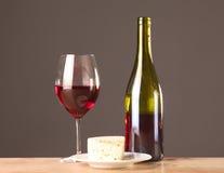 Botella y vidrio de vino en una tabla Fotos de archivo