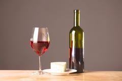 Botella y vidrio de vino en una tabla Imagen de archivo libre de regalías