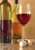 Botella y vidrio de vino en una tabla Imagenes de archivo