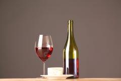 Botella y vidrio de vino en una tabla Fotos de archivo libres de regalías