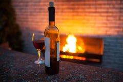 Botella y vidrio de vino rojo con el fuego en fondo; Imagen de archivo