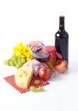 Botella y vidrio de vino rojo, de uvas y de queso aislados en blanco Foto de archivo libre de regalías