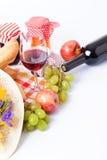Botella y vidrio de vino rojo, de uvas y de queso aislados en blanco Imagenes de archivo