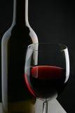 Botella y vidrio de vino sobre fondo negro Foto de archivo libre de regalías