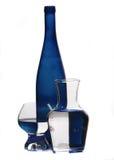 Botella y vidrios azules fotografía de archivo