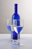 Botella y vidrios azules de vino Foto de archivo