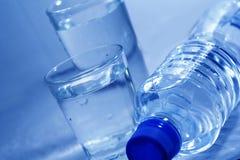 Botella y vidrios de agua Imagen de archivo libre de regalías