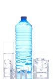 Botella y vidrios de agua mineral con los cubos de hielo Fotos de archivo libres de regalías