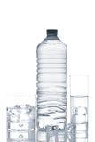 Botella y vidrios de agua mineral con los cubos de hielo Foto de archivo libre de regalías