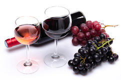 Botella y vidrios de vino con las uvas rojas y negras Foto de archivo